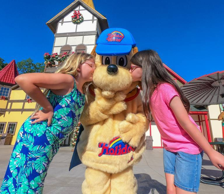 Two young girls giving Holidog a kiss